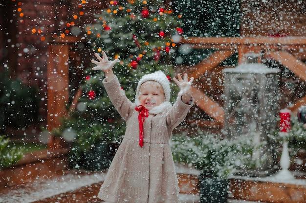 Jolie petite fille en manteau d'hiver et chapeau attraper la neige