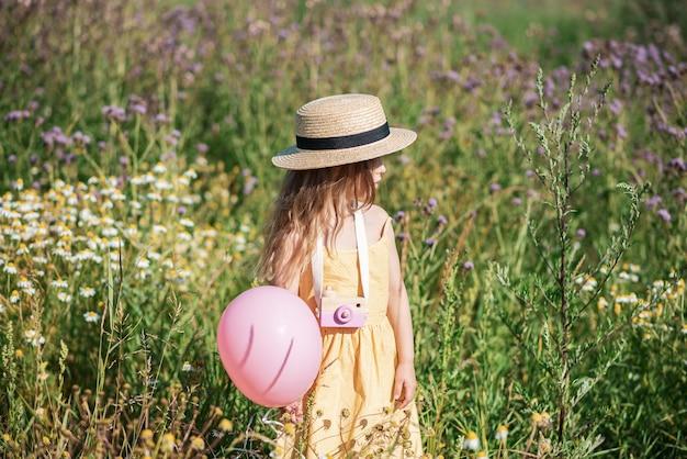 Jolie petite fille marchant dans le champ de fleurs en robe jaune et chapeau, heure d'été