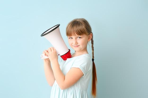 Jolie petite fille avec mégaphone sur la couleur