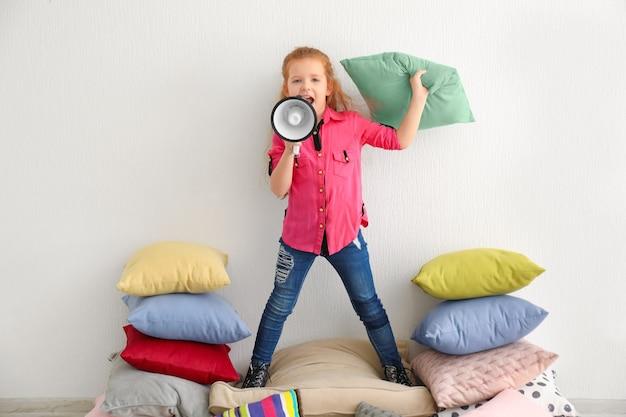 Jolie petite fille avec mégaphone debout sur une pile d'oreillers à l'intérieur
