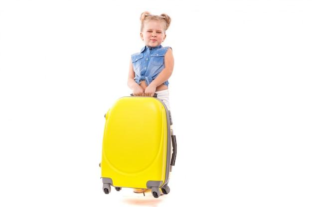 Jolie petite fille mignonne en chemise bleue, short blanc et lunettes de soleil se tenant près de la valise jaune