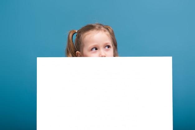 Jolie petite fille mignonne en chemise rose avec un singe et un pantalon bleu tenir affiche vide