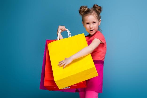 Jolie petite fille mignonne en robe rose est titulaire d'un sac en papier violet