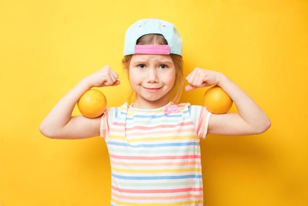 Jolie petite fille montre les biceps sur fond jaune. sentez-vous si puissant. concept de règles de filles. conseils d'éducation pour les filles. fort et puissant