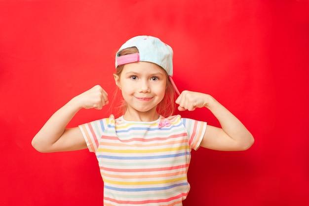Jolie petite fille montre les biceps sur fond rouge. sentez-vous si puissant. concept de règles de filles. conseils d'éducation pour les filles. fort et puissant