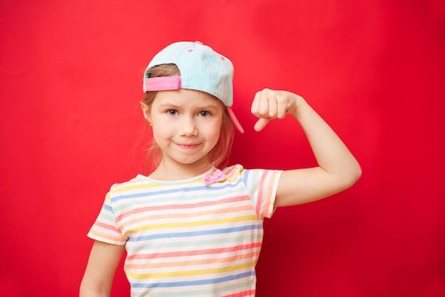 Jolie petite fille montre les biceps. sentez-vous si puissant. concept de règles de filles. conseils d'éducation pour les filles. fort et puissant