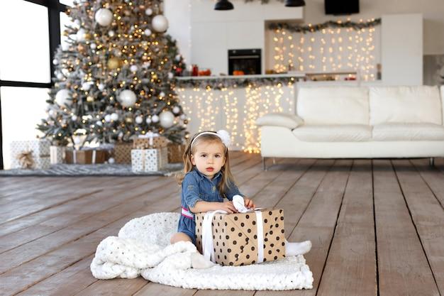 Jolie petite fille ouvrant ses cadeaux de noël
