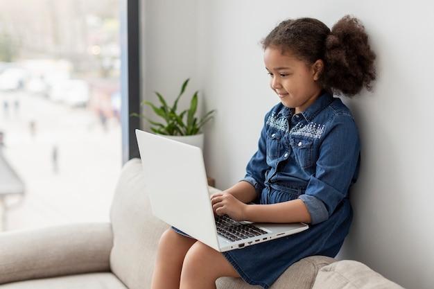 Jolie petite fille parcourant l'ordinateur portable à la maison