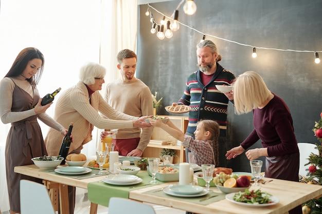 Jolie petite fille passant bol avec salade à son arrière-grand-mère par table de fête entre parents et grands-parents