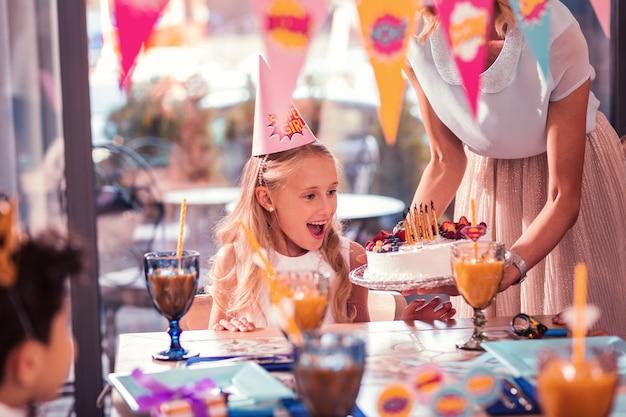 Jolie petite fille portant un chapeau de fête en regardant son gâteau d'anniversaire