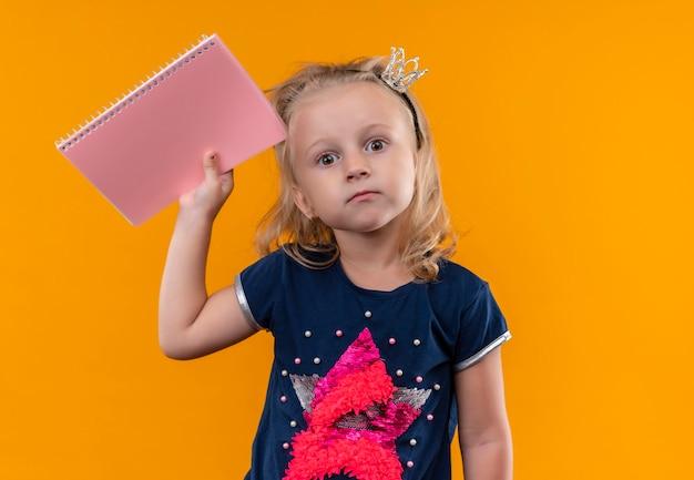 Une jolie petite fille portant une chemise bleu marine en bandeau couronne montrant un cahier rose sur un mur orange