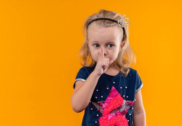 Une jolie petite fille portant une chemise bleu marine en bandeau couronne montrant chut geste avec l'index sur la bouche et à côté sur un mur orange