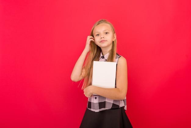 Jolie petite fille portant des vêtements d'été debout sur rouge, tenant un livre -