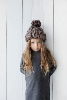 Jolie petite fille posant à côté d'un mur blanc