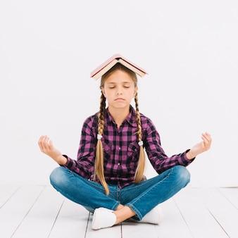 Jolie petite fille posant avec un livre sur la tête