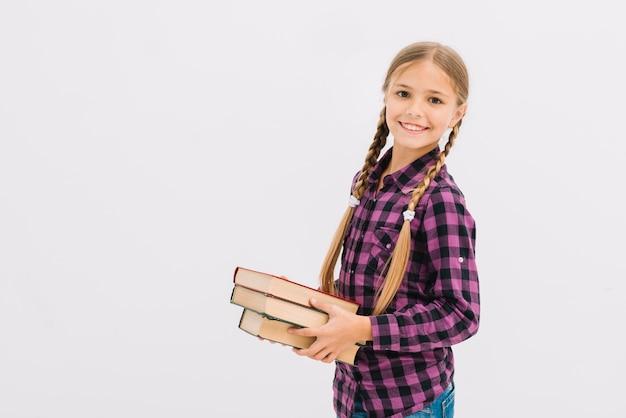 Jolie petite fille posant avec des livres