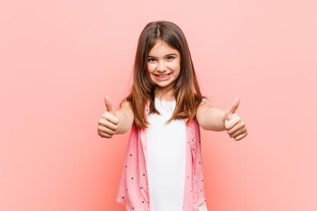 Jolie petite fille avec le pouce levé, acclamations à propos de quelque chose, concept de soutien et de respect.