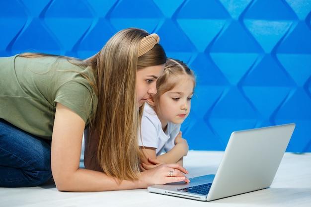 Jolie petite fille prête à utiliser le clavier de l'ordinateur portable assise sur le sol de la cuisine avec sa mère aimante