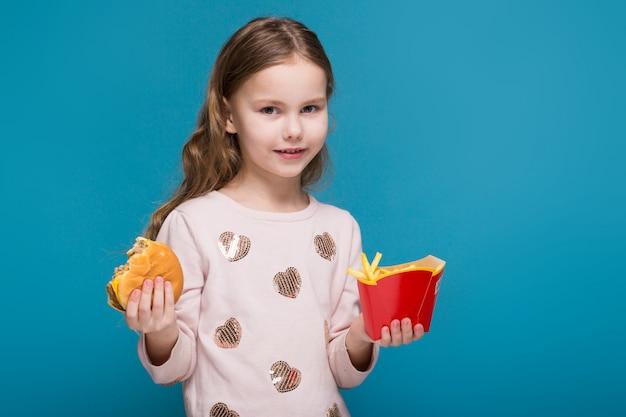 Jolie petite fille en pull aux cheveux bruns tient un hamburger