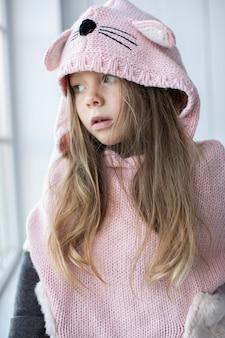 Jolie petite fille en pull rose