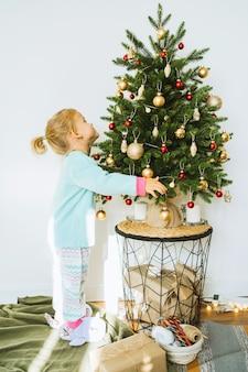 Une jolie petite fille en pyjama décore un arbre de noël avec des boules dans la chambre joyeux noël et bonne année concept espace pour le texte moments agréables en famille