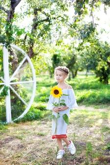 Jolie petite fille avec une queue de cochon sur la tête tient un enfant tournesol avec un tournesol dans le jardin