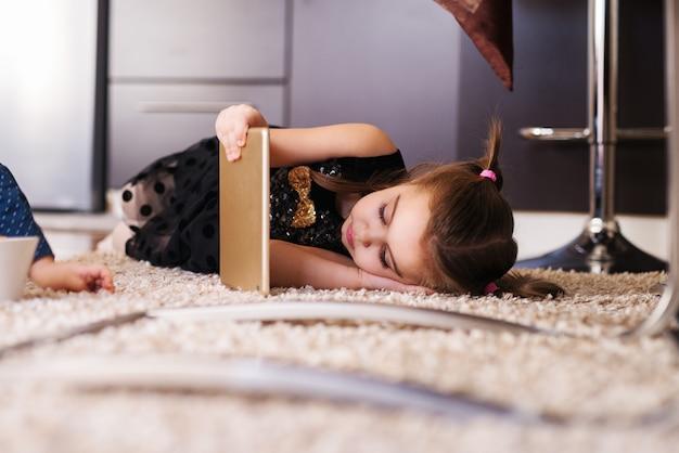Jolie petite fille avec des queues de cheval en regardant la tablette en position couchée sur le tapis.