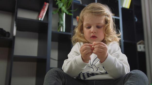 Jolie petite fille de race blanche aux cheveux bouclés blonds implantée sur le sol et ouvrant l'emballage avec des jouets sur fond vivant. intérieur.