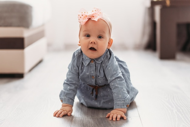 Une jolie petite fille rampe sur le sol dans la pièce. un enfant apprend à ramper