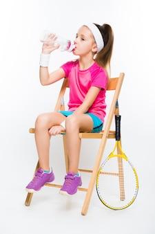 Jolie petite fille avec une raquette de tennis sur blanc