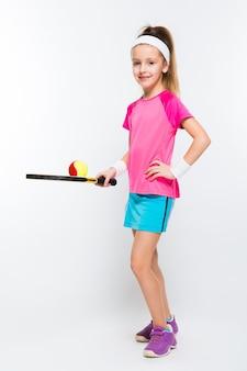 Jolie petite fille avec une raquette de tennis dans ses mains sur un mur blanc