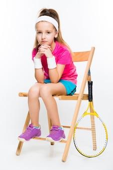 Jolie petite fille avec une raquette de tennis