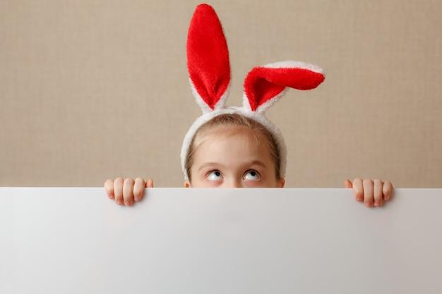 Une jolie petite fille regarde à cause d'une bannière vide dans laquelle vous pouvez insérer n'importe quel texte.