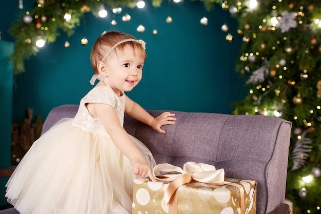 Jolie petite fille en robe blanche jouant et se réjouissant de l'arbre de noël et des lumières.