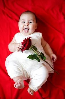 Jolie petite fille en robe blanche avec rose rouge