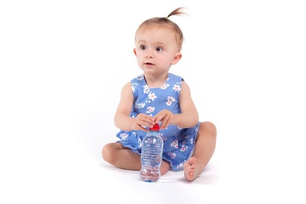 Jolie petite fille en robe bleue avec de l'eau