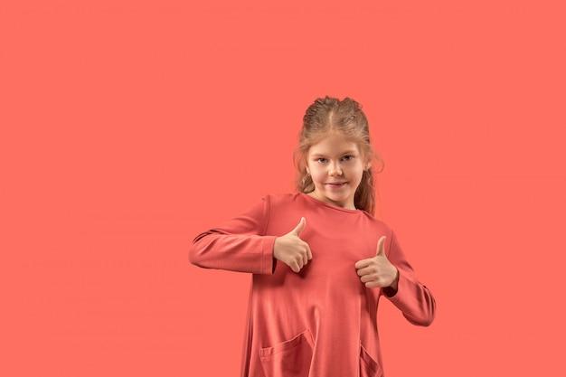 Jolie petite fille en robe corail aux cheveux longs souriant