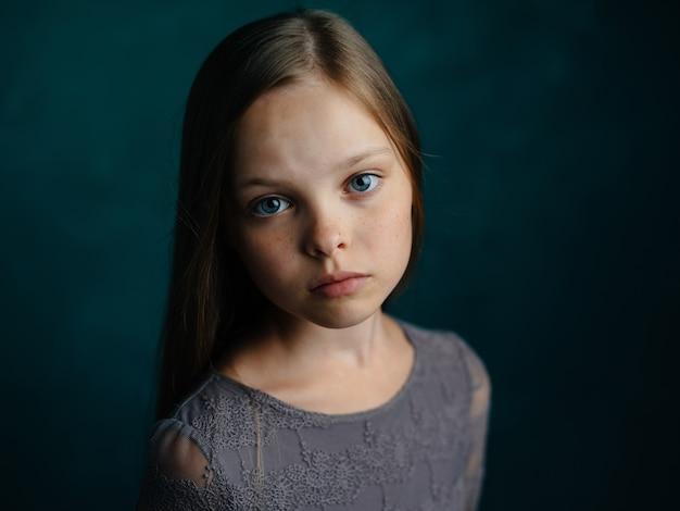 Jolie petite fille en robe grise portrait de cheveux lâches vue recadrée. photo de haute qualité