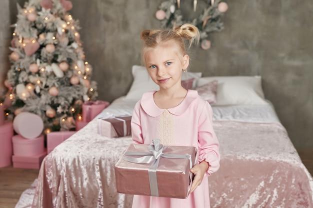 Jolie petite fille en robe rose avec présent sur fond d'arbre de noël. joyeux noël et bonnes fêtes! concept sain et d'hiver de bébé. noël en famille.