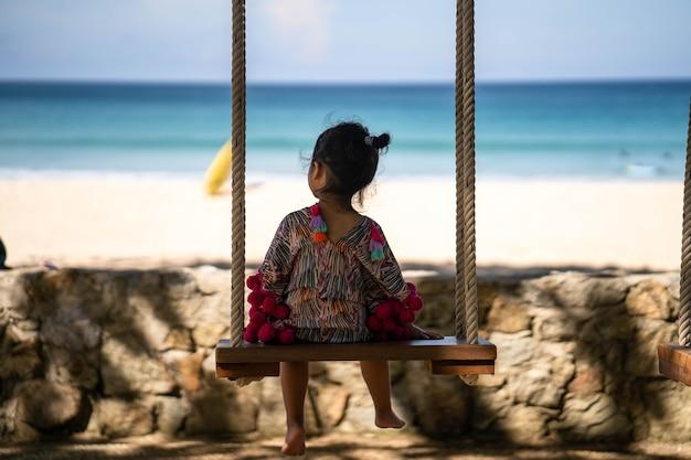 Jolie petite fille en robe rouge assise sur la balançoire