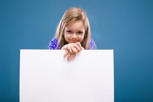 Jolie petite fille en robe violette est titulaire d'une affiche vide
