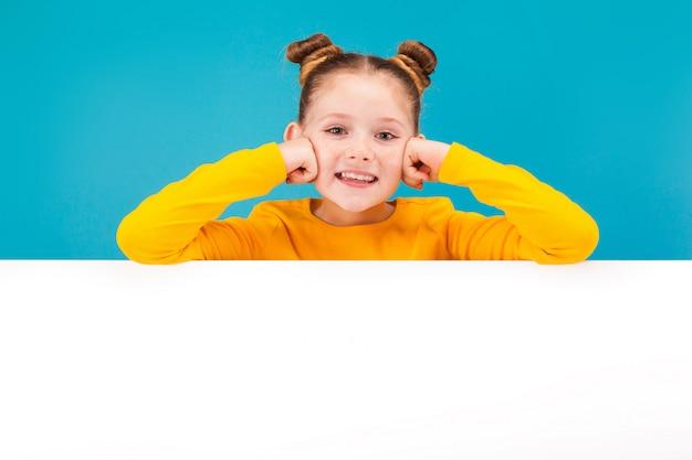 Jolie petite fille rousse en pull jaune
