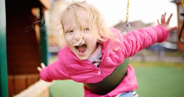 Jolie petite fille s'amusant sur une aire de jeux extérieure
