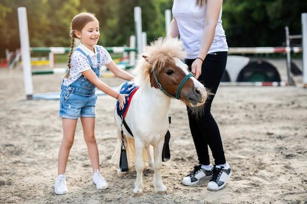 Jolie petite fille et sa sœur aînée s'amusant avec un cheval poney à l'extérieur au ranch.