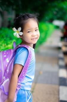 Jolie petite fille avec sac à dos marchant dans le parc prêt pour la rentrée scolaire
