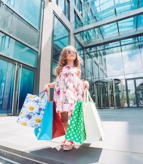 Jolie petite fille avec des sacs à provisions