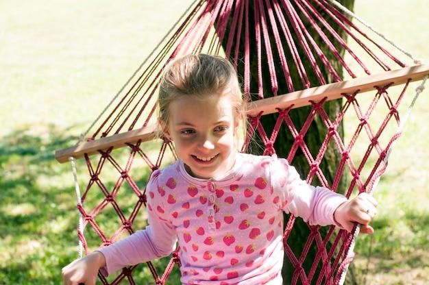 Jolie petite fille se balançant sur une balançoire dans le jardin
