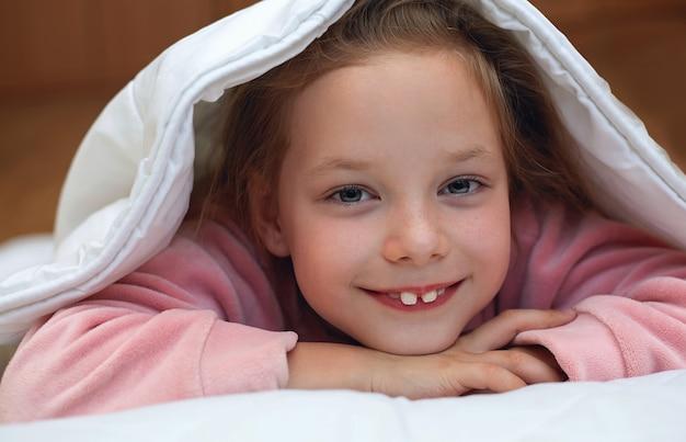 Jolie petite fille se cachant sous la couverture