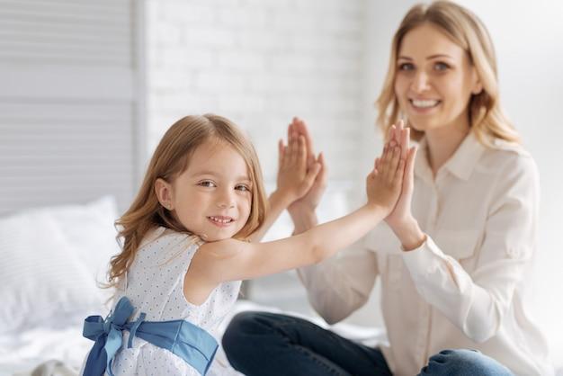 Jolie petite fille se liant à sa mère en appuyant ses paumes contre les paumes de sa mère tout en regardant de face avec un large sourire.