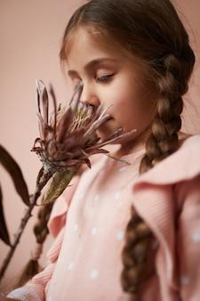 Jolie petite fille sentant la fleur